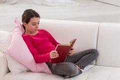 Muchacha adolescente que se sienta en el sofá en casa y que lee a Fotografía de archivo