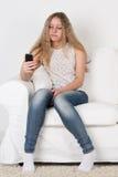 Muchacha adolescente que se sienta en el sofá y que mira el teléfono Imagen de archivo