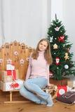 Muchacha adolescente que se sienta en el trineo con los presentes y el árbol de navidad Foto de archivo