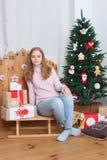 Muchacha adolescente que se sienta en el trineo con los presentes y el árbol de navidad Imagenes de archivo
