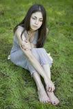 Muchacha adolescente que se sienta en hierba Foto de archivo libre de regalías