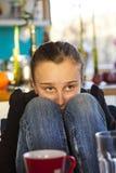 Muchacha adolescente que se sienta en la cocina Imagen de archivo