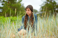 Muchacha adolescente que se sienta en la hierba Fotos de archivo libres de regalías