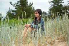 Muchacha adolescente que se sienta en la hierba Fotografía de archivo libre de regalías