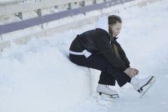Muchacha adolescente que se sienta en la nieve que aprieta los cordones en los patines Fotos de archivo