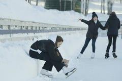 Muchacha adolescente que se sienta en la nieve que aprieta los cordones en los patines Fotografía de archivo