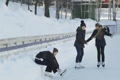 Muchacha adolescente que se sienta en la nieve que aprieta los cordones en los patines Imagen de archivo libre de regalías