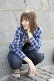muchacha adolescente que se sienta en la pared de piedra Foto de archivo libre de regalías