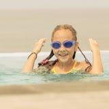 Muchacha adolescente que se sienta en la piscina Imagenes de archivo