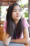 Muchacha adolescente que se sienta en la tabla, pensando Imagenes de archivo
