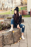 Muchacha adolescente que se sienta en las escaleras contra la pared del grunge Foto de archivo libre de regalías