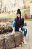 Muchacha adolescente que se sienta en las escaleras contra la pared del grunge Fotografía de archivo