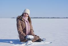 Muchacha adolescente que se sienta en nieve Fotos de archivo