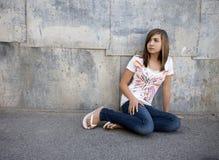 Muchacha adolescente que se sienta en pasillo Imagenes de archivo