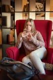 Muchacha adolescente que se sienta en silla y que mira el teléfono Imagen de archivo libre de regalías