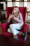 Muchacha adolescente que se sienta en silla y que mira el teléfono Foto de archivo