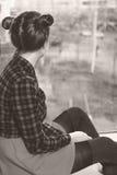 Muchacha adolescente que se sienta en travesaño de la ventana imagen monocromática Imagen de archivo libre de regalías