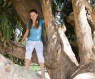 Muchacha adolescente que se sienta en un árbol Fotografía de archivo libre de regalías