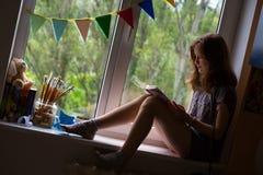 Muchacha adolescente que se sienta en un alféizar Fotos de archivo