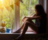 Muchacha adolescente que se sienta en un alféizar Imagen de archivo libre de regalías