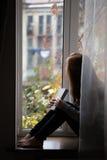 Muchacha adolescente que se sienta en un alféizar Imagen de archivo
