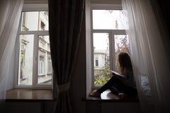 Muchacha adolescente que se sienta en un alféizar Fotos de archivo libres de regalías