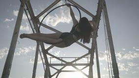 Muchacha adolescente que se sienta en un anillo para la acrobacia aérea, visión inferior almacen de video