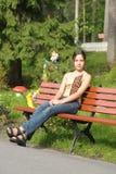 Muchacha adolescente que se sienta en un banco Imagen de archivo libre de regalías