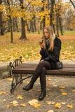 Muchacha adolescente que se sienta en un banco de parque en la caída con un smartphone Fotografía de archivo