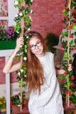 Muchacha adolescente que se sienta en un oscilación Fotografía de archivo