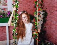 Muchacha adolescente que se sienta en un oscilación Imágenes de archivo libres de regalías
