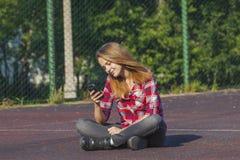 Muchacha adolescente que se sienta en un patio de la escuela Imagen de archivo