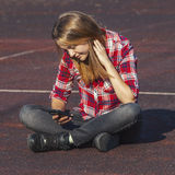 Muchacha adolescente que se sienta en un patio de la escuela Foto de archivo libre de regalías