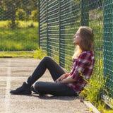 Muchacha adolescente que se sienta en un patio de la escuela Foto de archivo