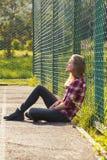Muchacha adolescente que se sienta en un patio de la escuela Imágenes de archivo libres de regalías