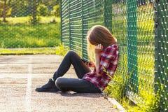 Muchacha adolescente que se sienta en un patio de la escuela Imagenes de archivo