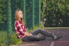Muchacha adolescente que se sienta en un patio de la escuela Fotografía de archivo