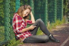 Muchacha adolescente que se sienta en un patio de la escuela Fotos de archivo