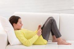 Muchacha adolescente que se sienta en un sofá en casa y la lectura Fotos de archivo libres de regalías