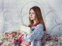 Muchacha adolescente que se sienta en una cama Fotografía de archivo