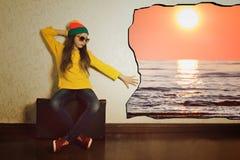 Muchacha adolescente que se sienta en una maleta antes de viaje del día de fiesta Foto de archivo libre de regalías