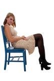 Muchacha adolescente que se sienta en una silla azul Foto de archivo libre de regalías