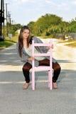 Muchacha adolescente que se sienta en una silla en un camino (1) Foto de archivo libre de regalías