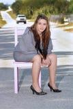 Muchacha adolescente que se sienta en una silla en un camino (2) Foto de archivo