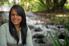 Muchacha adolescente que se sienta por el arroyo Foto de archivo libre de regalías