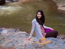Muchacha adolescente que se sienta por el río en Tailandia Fotos de archivo