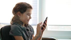 Muchacha adolescente que se sienta por el smartphone de la ventana que juega a los juegos onlines Fotografía de archivo libre de regalías