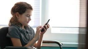 Muchacha adolescente que se sienta por la ventana con el smartphone que juega a los juegos onlines Fotos de archivo