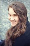 Muchacha adolescente que se sienta por una charca llenada de las rocas Imagenes de archivo
