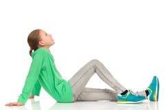 Muchacha adolescente que se sienta que mira para arriba Fotografía de archivo